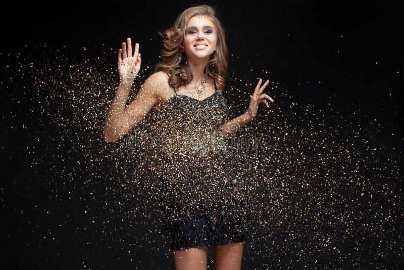 Lycklig ung kvinna i en aftonklänning som firar nytt år royaltyfria foton