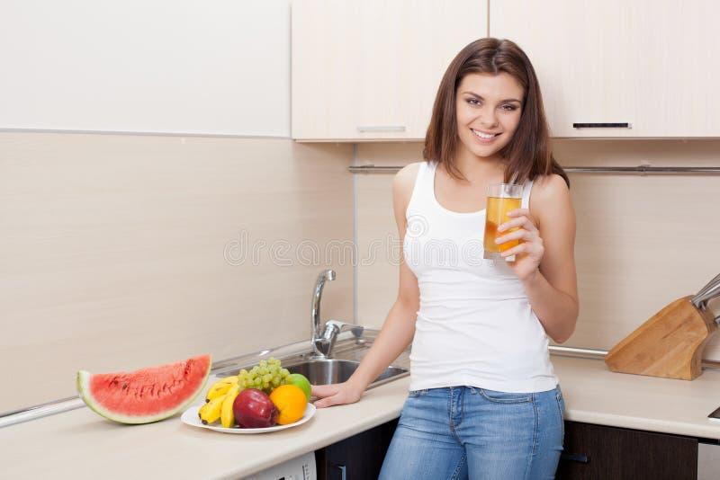 Lycklig ung kvinna i en dricka fruktsaft för kök arkivfoto