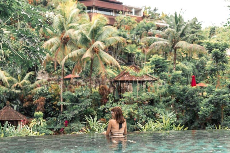 Lycklig ung kvinna i en tropisk oändlighetspöl Lyxig semesterort på den Bali ön arkivfoton