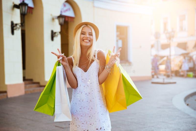 Lycklig ung kvinna i hållande shoppingpåsar för hatt, medan gå royaltyfria bilder