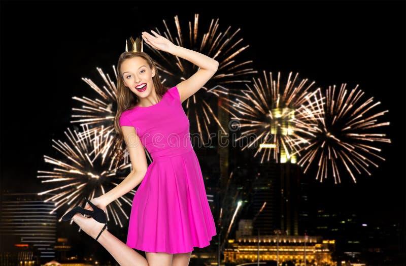 Lycklig ung kvinna i krona över fyrverkerit på natten royaltyfria foton