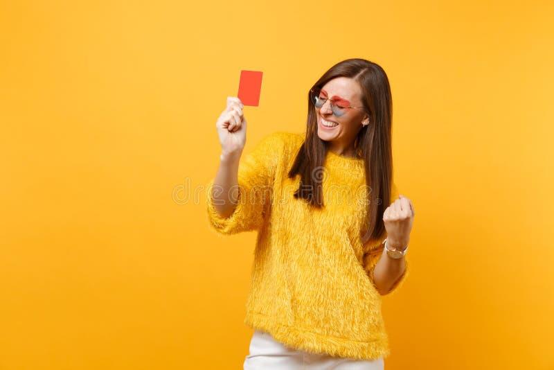 Lycklig ung kvinna i pälströja- och hjärtaglasögon som griper hårt om näven som vinnareinnehavkreditkorten som isoleras på ljust royaltyfria bilder