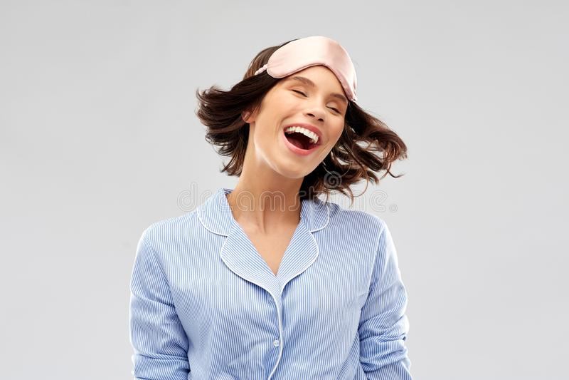 Lycklig ung kvinna i pajama och ?ga som sover maskeringen royaltyfri fotografi