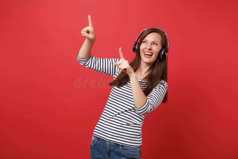 Lycklig ung kvinna i randig kläder med lyssnande musik för trådlös hörlurar som pekar pekfingrar som åt sidan isoleras på royaltyfria foton