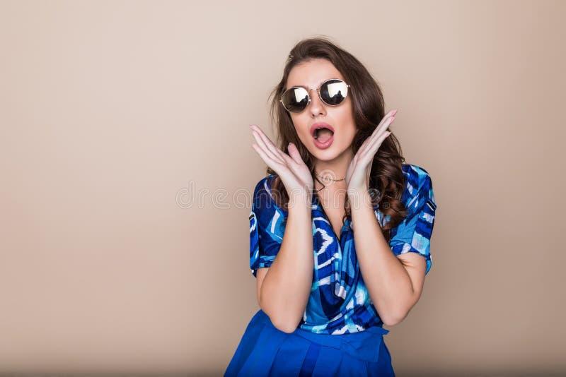 Lycklig ung kvinna i solglasögon som ser upphetsad blick på kameran på färgstudiobakgrund Kroppsspråk royaltyfri fotografi
