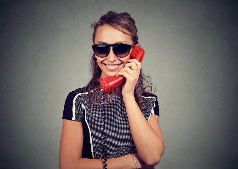 Lycklig ung kvinna i solglasögon som talar på en telefon royaltyfri bild