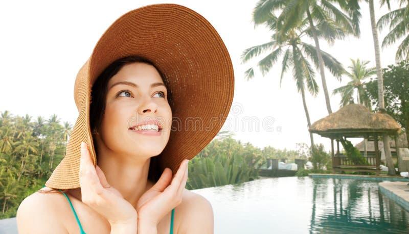 Lycklig ung kvinna i sugrörhatt på den tropiska stranden arkivbild