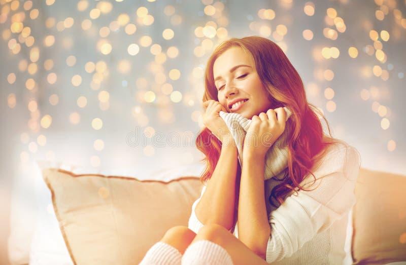 Lycklig ung kvinna i varm sweater hemma royaltyfria bilder