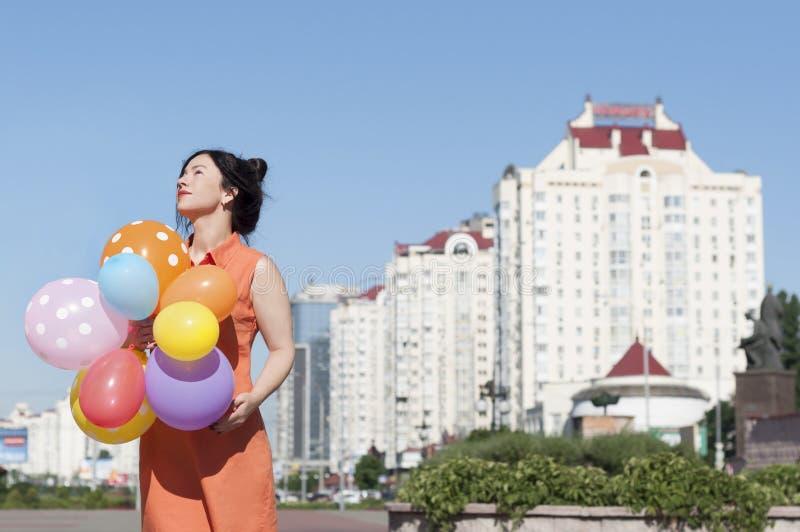 Lycklig ung kvinna med ballonger på stadsfyrkanten arkivbild