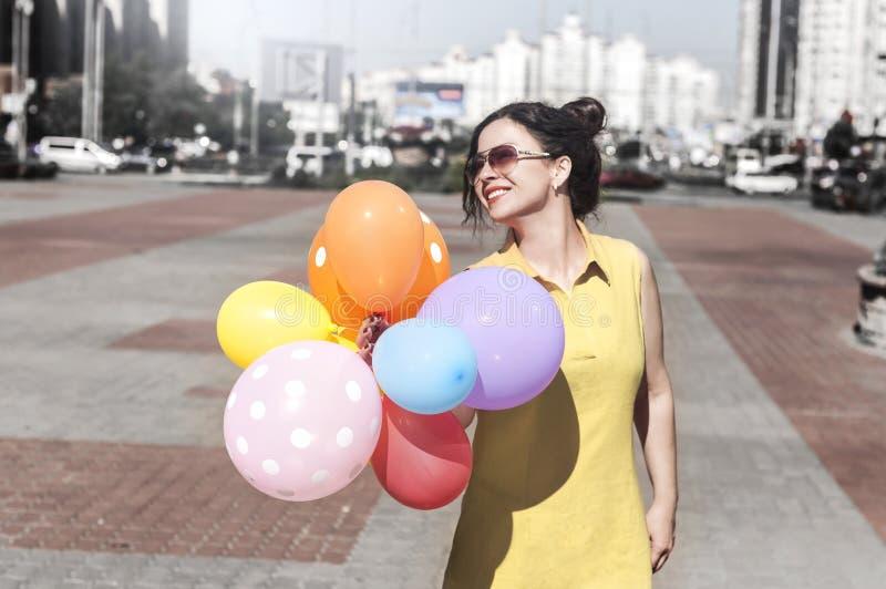 Lycklig ung kvinna med ballonger på stadsfyrkanten royaltyfria bilder