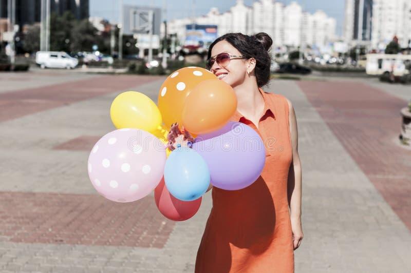 Lycklig ung kvinna med ballonger på stadsfyrkanten royaltyfri bild