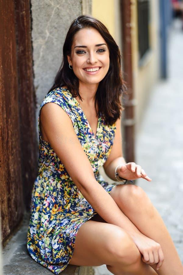 Lycklig ung kvinna med blåa ögon som ler sammanträde på stads- moment royaltyfri bild