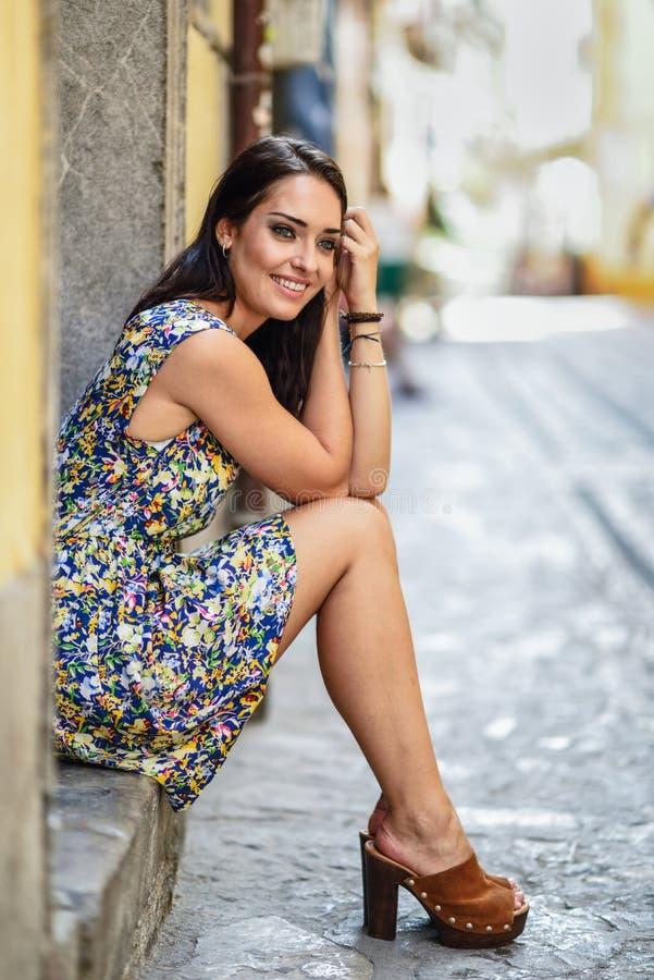 Lycklig ung kvinna med blåa ögon som ler sammanträde på stads- moment royaltyfri foto