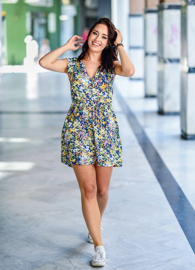 Lycklig ung kvinna med blåa ögon som utomhus ler Bärande blommaklänning för flicka i stads- bakgrund fotografering för bildbyråer
