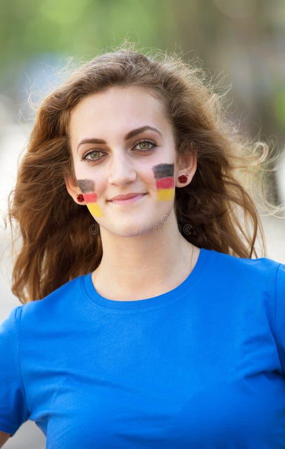 Lycklig ung kvinna med den tyska flaggan på kinder Gladlynt multiraci arkivfoton