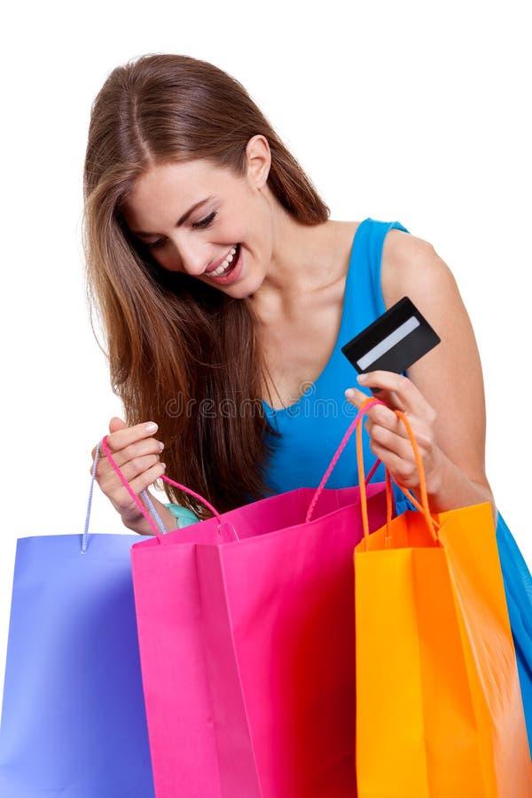 Lycklig ung kvinna med det isolerade färgrika visumet för shoppingpåsar royaltyfri foto