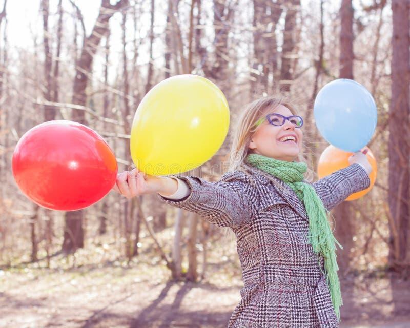 Lycklig ung kvinna med färgrika ballonger royaltyfri fotografi