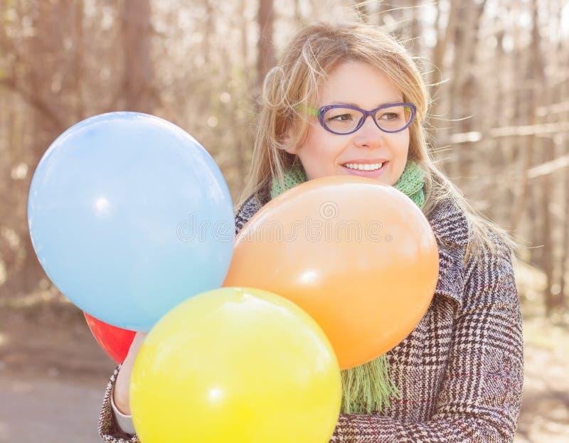 Lycklig ung kvinna med färgrika ballonger arkivbild