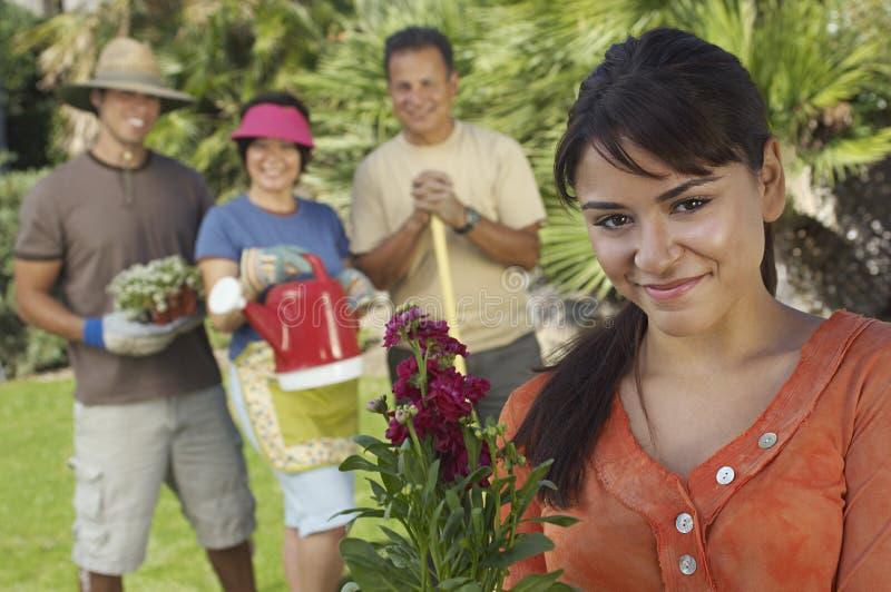 Lycklig ung kvinna med familjen i trädgård royaltyfria bilder