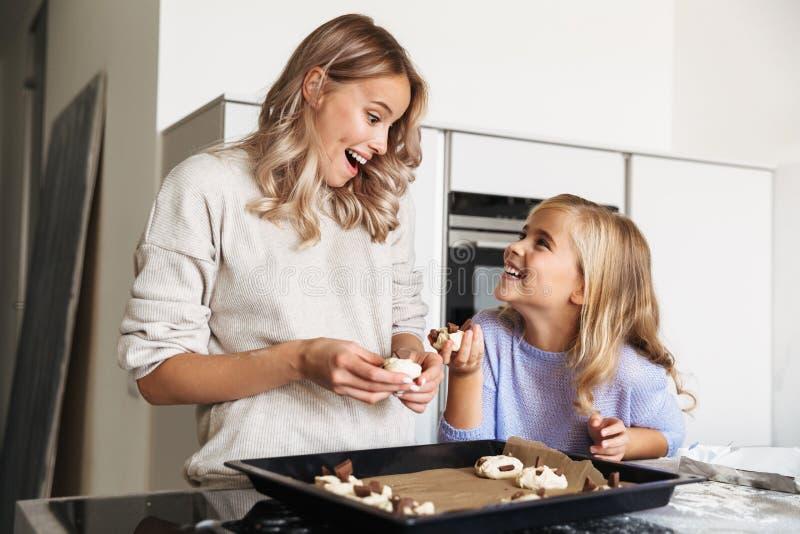 Lycklig ung kvinna med hennes lilla hemmastadda kök för syster som inomhus lagar mat raringbagerit royaltyfria bilder