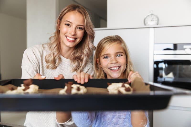 Lycklig ung kvinna med hennes lilla hemmastadda kök för syster som inomhus lagar mat raringbagerit arkivfoton