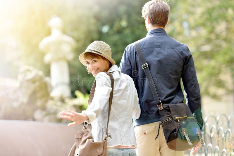 Lycklig ung kvinna med hennes pojkvän som går i parkera royaltyfria foton