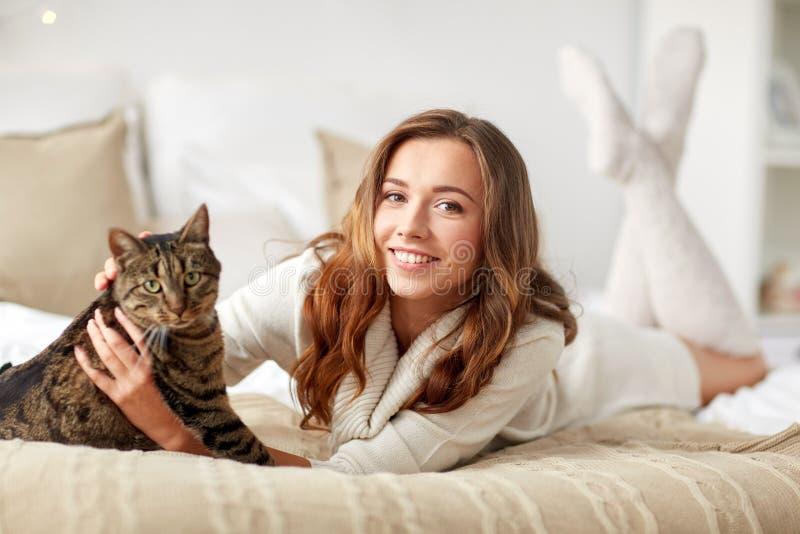 Lycklig ung kvinna med katten som hemma ligger i säng arkivfoton