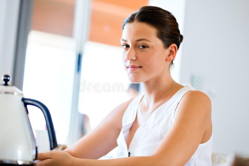 Lycklig ung kvinna med kopp te eller kaffe hemma royaltyfri bild