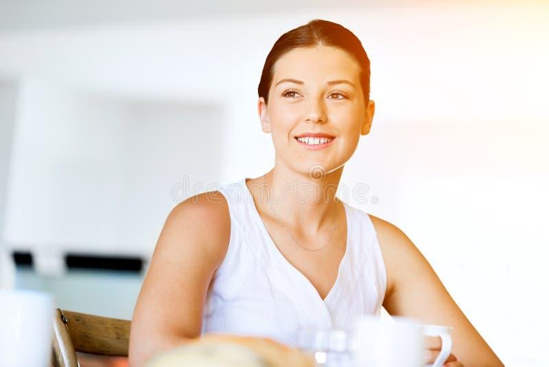 Lycklig ung kvinna med kopp te eller kaffe hemma arkivbilder