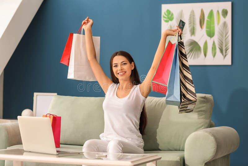 Lycklig ung kvinna med kreditkort- och shoppingpåsar som hemma sitter på soffan royaltyfri foto