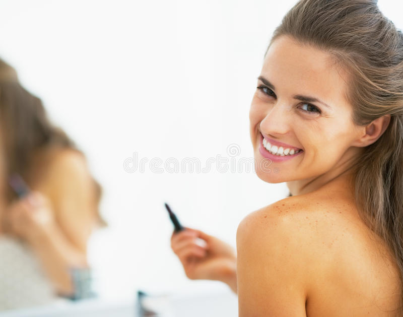 Lycklig ung kvinna med läppstift i badrum royaltyfri bild