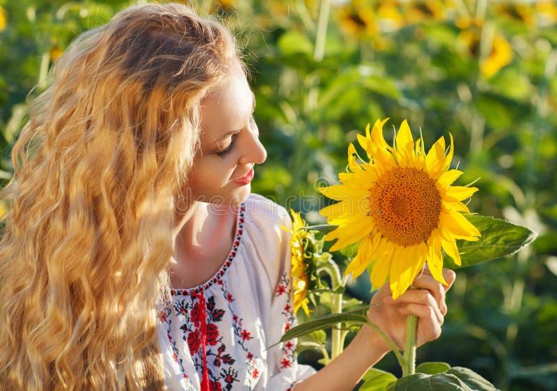 Lycklig ung kvinna med långt hår i solrosfältet royaltyfria foton