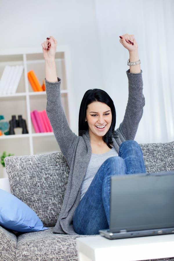 Lycklig ung kvinna med lyftta händer.