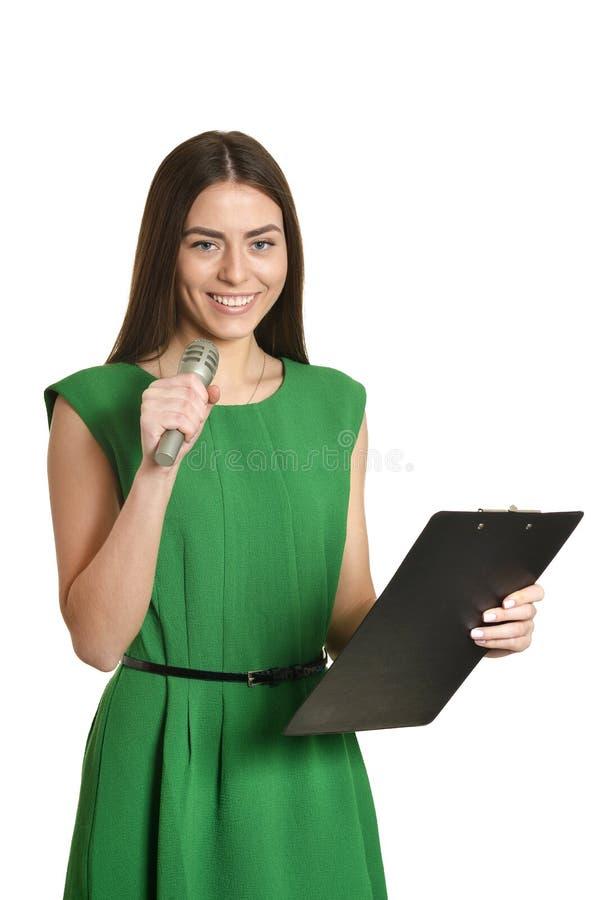 Lycklig ung kvinna med mikrofonen på vit bakgrund arkivbild
