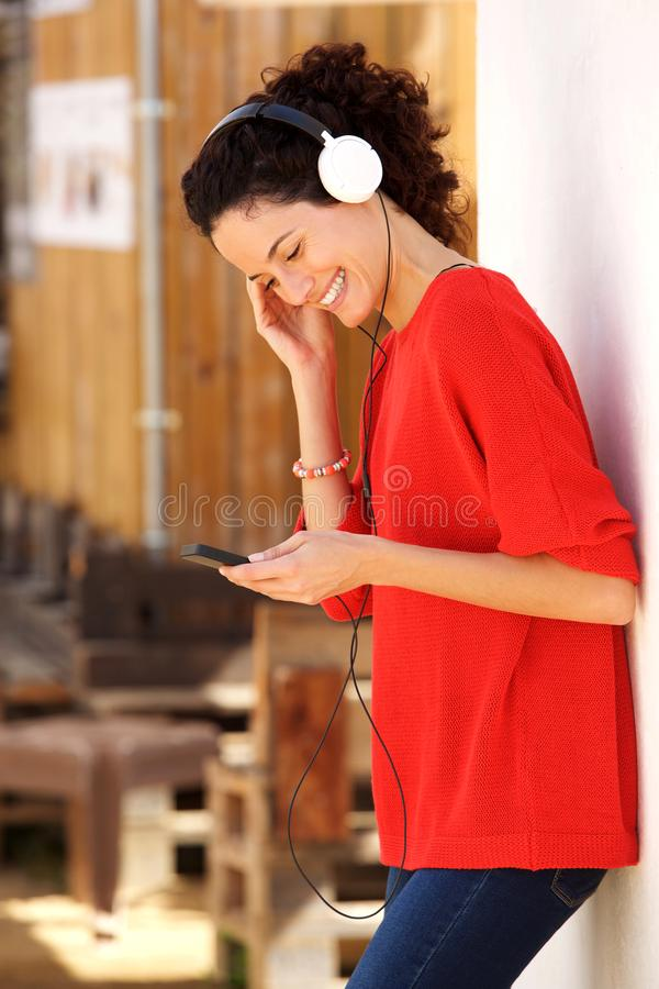 Lycklig ung kvinna med mobiltelefonen och hörlurar fotografering för bildbyråer