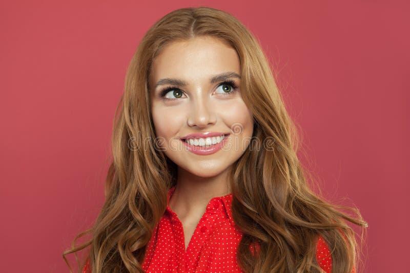 Lycklig ung kvinna med röd fröjd för lockigt hår på positiv nyheterna och att se upp med glat och charmigt leende Ljust rödbrun s royaltyfria bilder