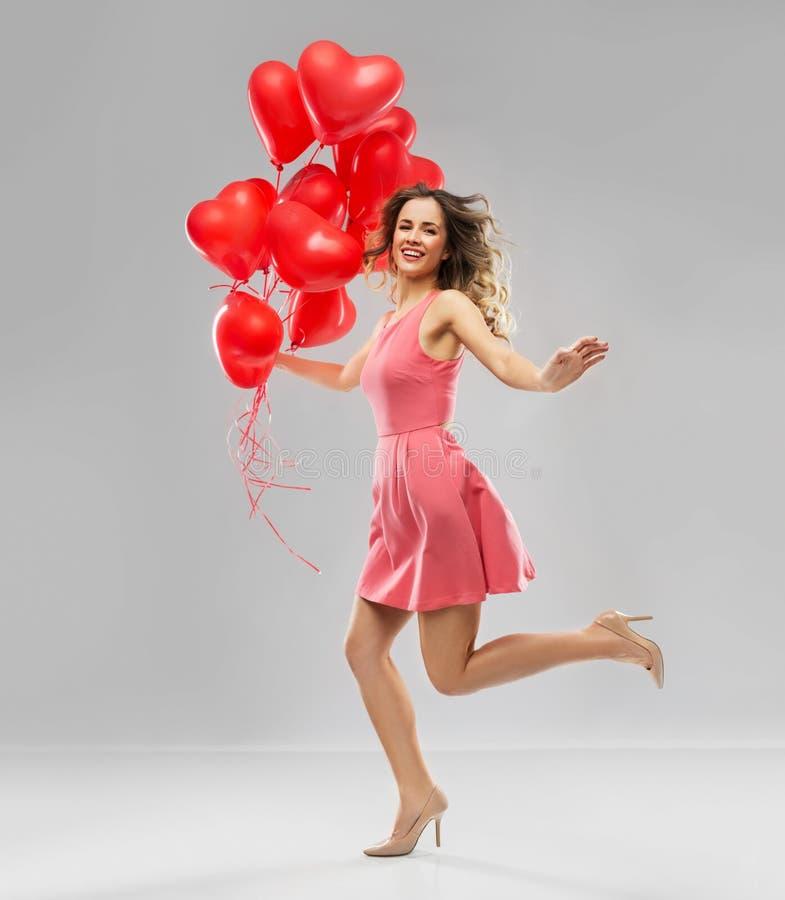 Lycklig ung kvinna med röd hjärta formade ballonger arkivbild