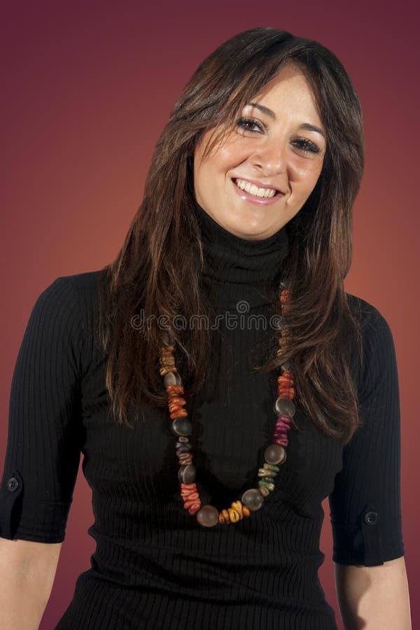 Lycklig ung kvinna med raksträckabrunt på brun bakgrund royaltyfri foto