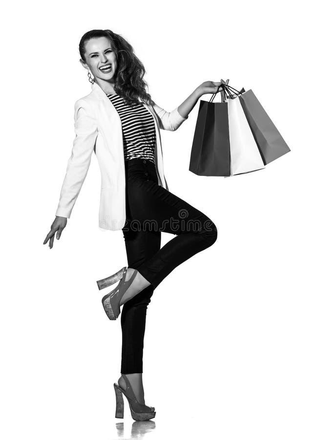 Lycklig ung kvinna med shoppingpåsar som poserar på vit bakgrund royaltyfri fotografi