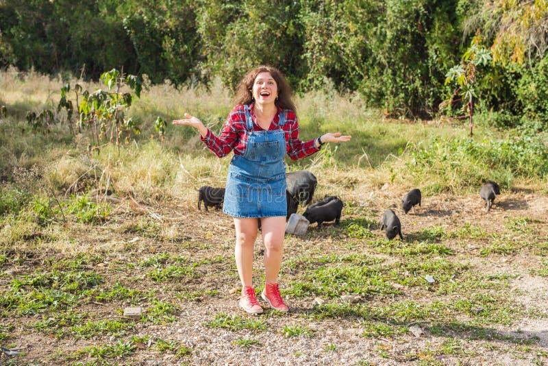Lycklig ung kvinna med små vildsvin på bakgrund royaltyfri fotografi