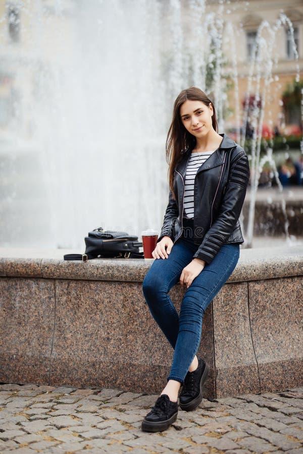 Lycklig ung kvinna mot en stadsspringbrunn stads- stil arkivbild