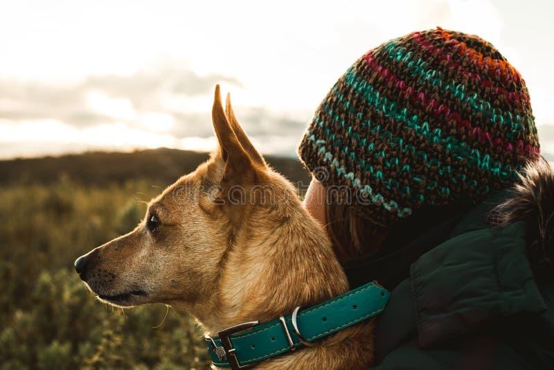 Lycklig ung kvinna och att kyssa och krama hennes hund Begrepp av förälskelse mellan kvinnan och hunden royaltyfri foto