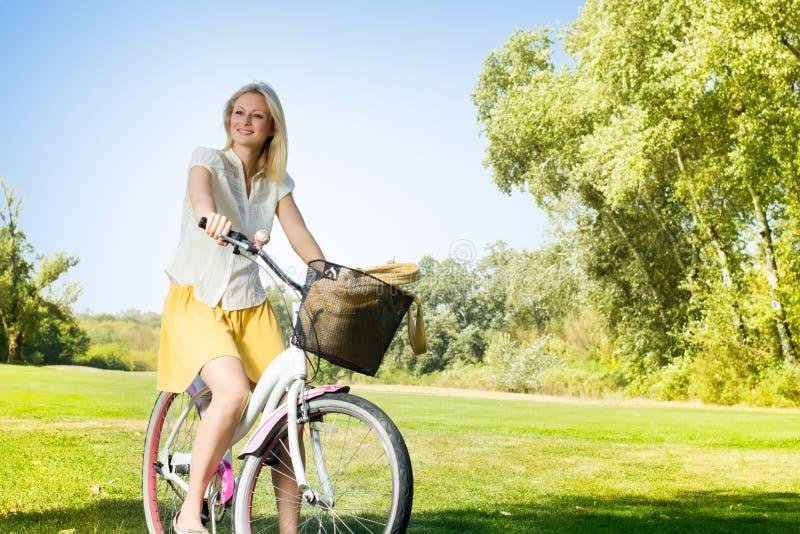 Lycklig ung kvinna på cykeln royaltyfri bild