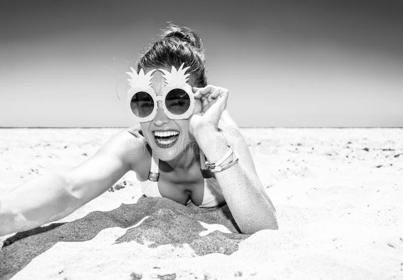 Lycklig ung kvinna på seacoasten som tar selfie royaltyfri fotografi