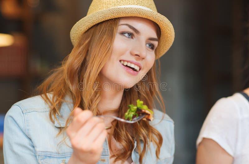 Lycklig ung kvinna som äter sallad på stången eller baren arkivbilder