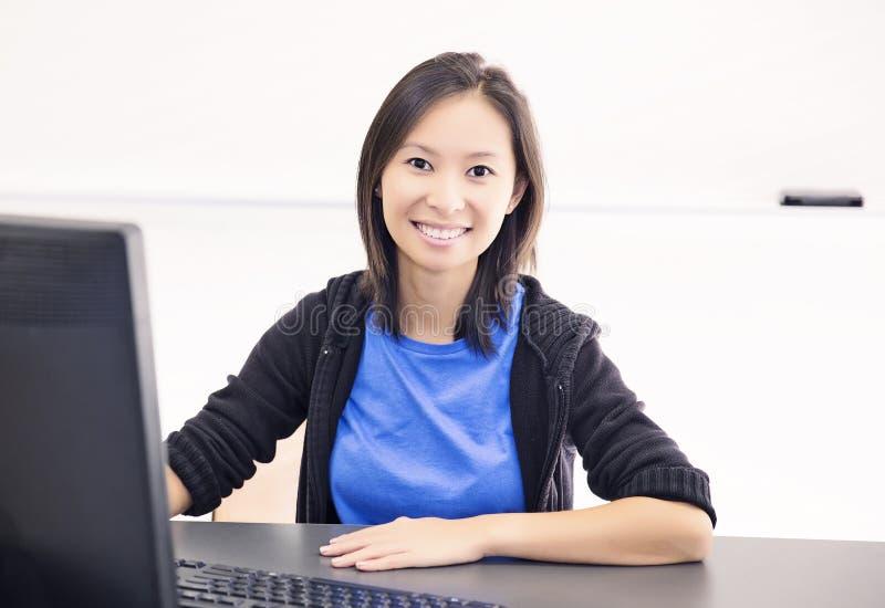 Lycklig ung kvinna som använder datoren fotografering för bildbyråer