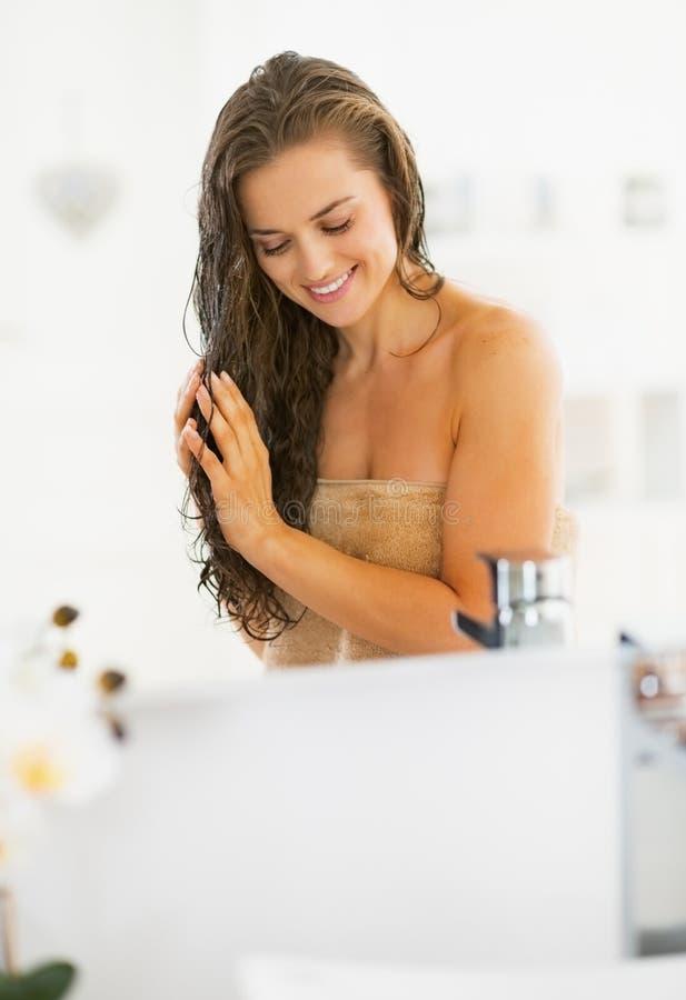 Lycklig ung kvinna som applicerar hårmaskeringen i badrum royaltyfri bild