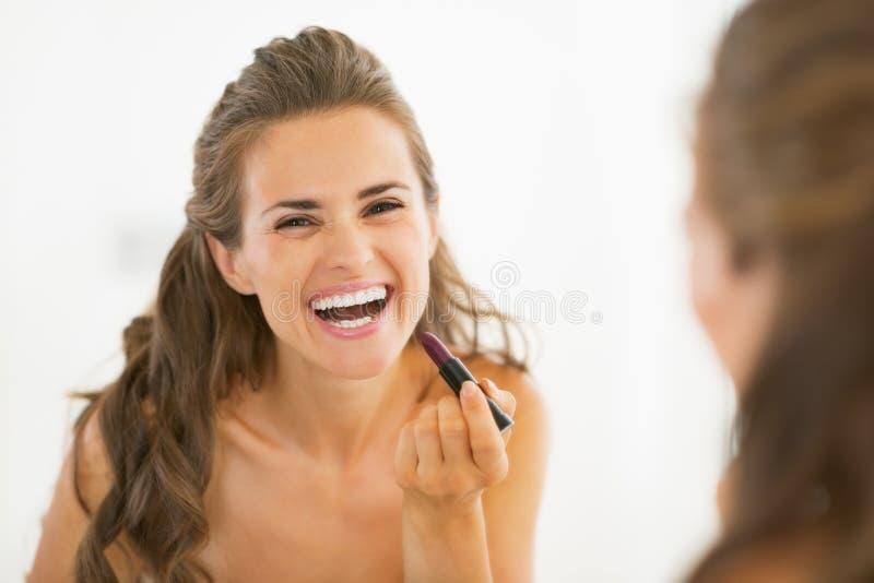Lycklig ung kvinna som applicerar läppstift i badrum arkivbilder