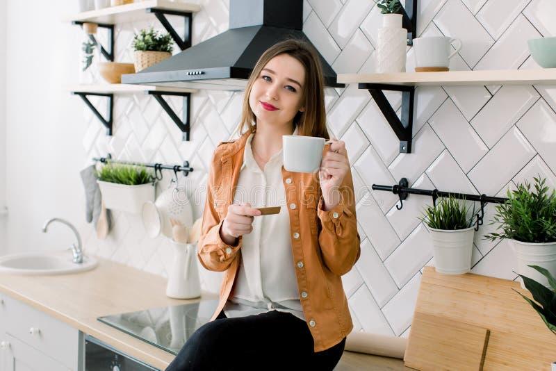 Lycklig ung kvinna som dricker kaffe, medan sitta p? k?ket hemma i morgonen arkivfoton