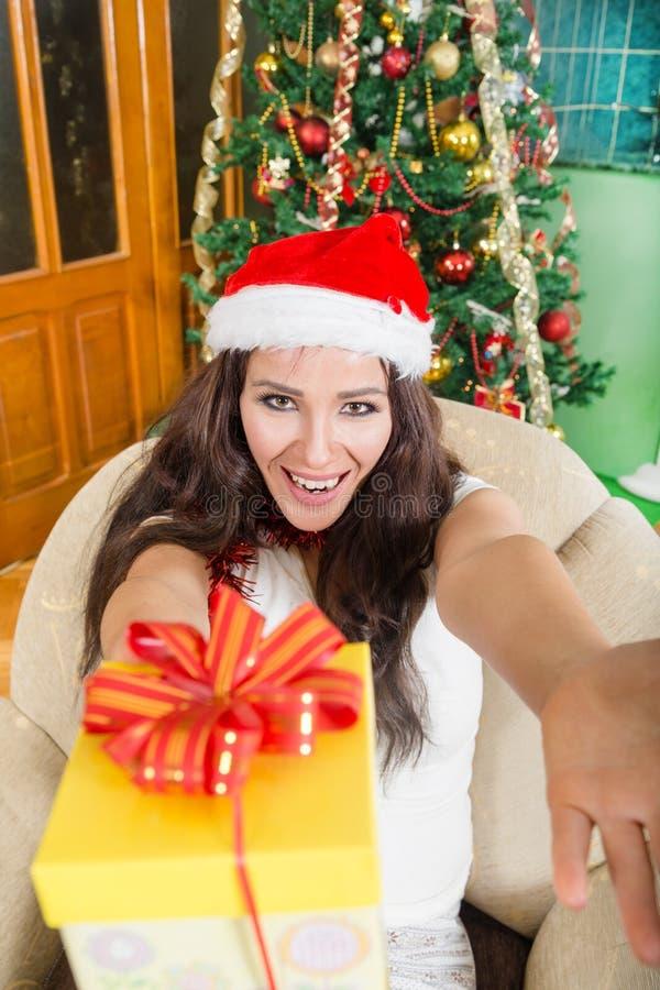 Lycklig ung kvinna som erbjuder gåvaasken med glädje och generositet royaltyfri foto